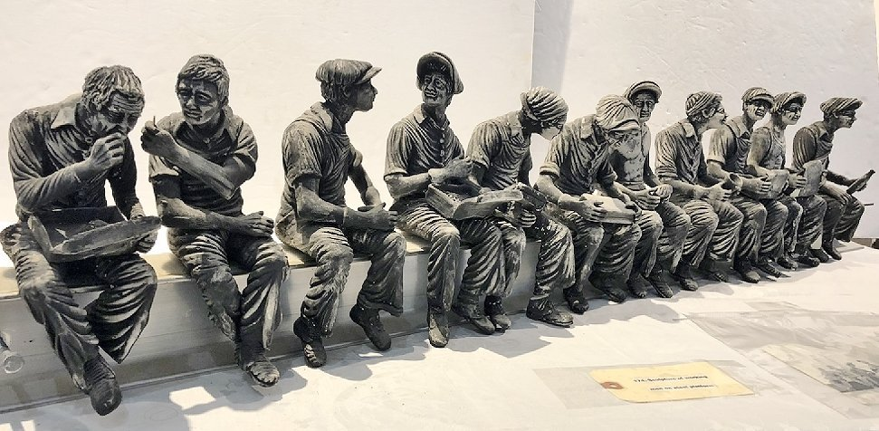 Sculpture of working men lunch on steel beam by Furnari