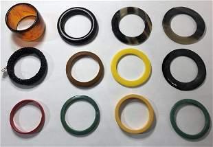 Twelve old plastic bracelets