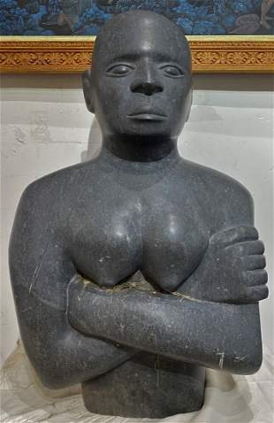 Large stone sculpture of African youth, folded arms