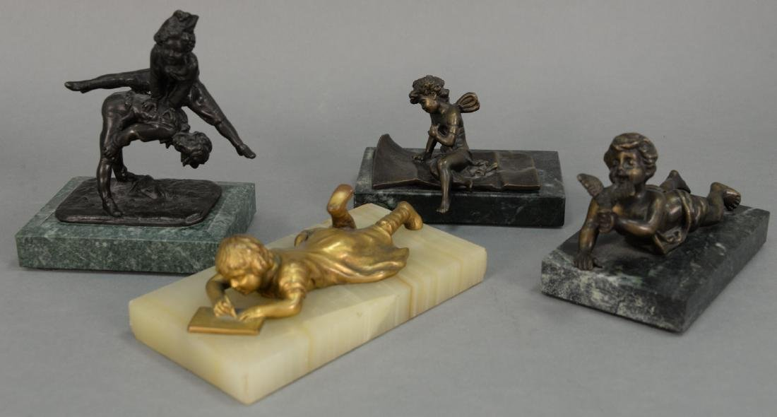 Four bronze figures including cherub seated on folded