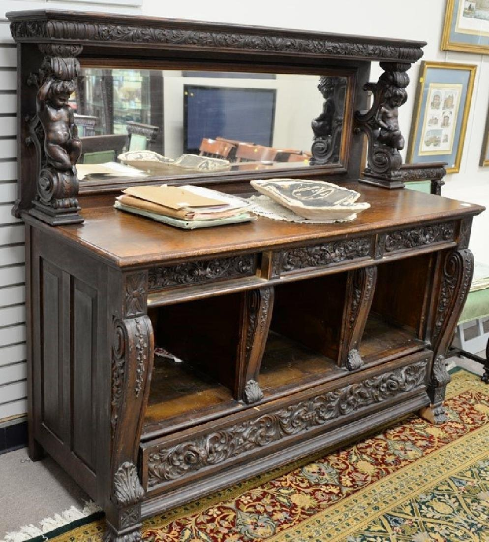 Oak sideboard with mirror back and putti shelf supports