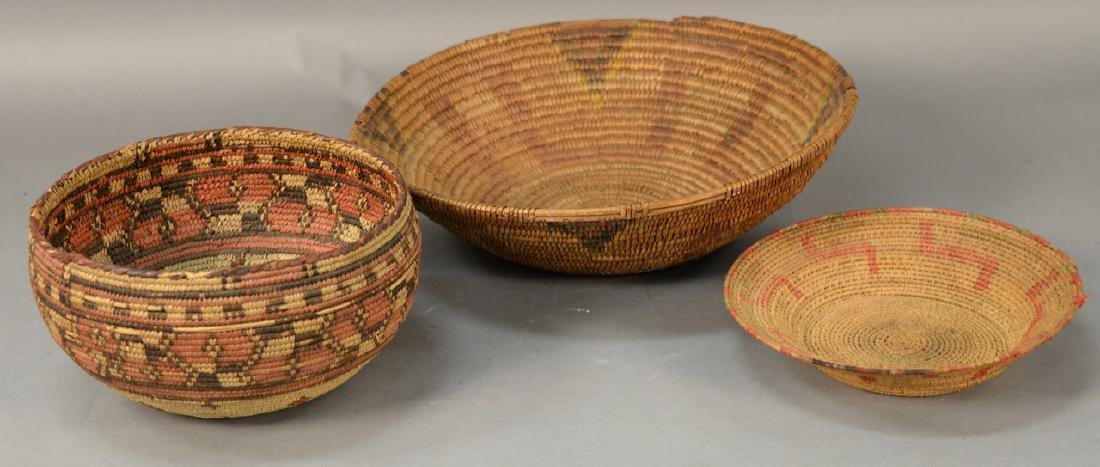 Three coiled Indian baskets, each with decoration.