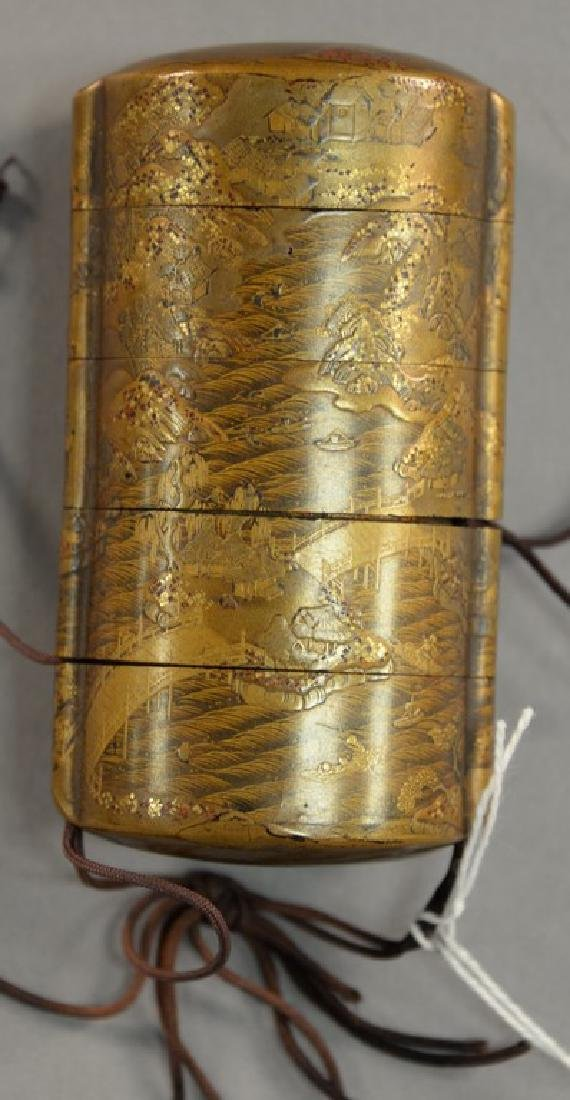 Japanese lacquered inro with gold landscape scene on