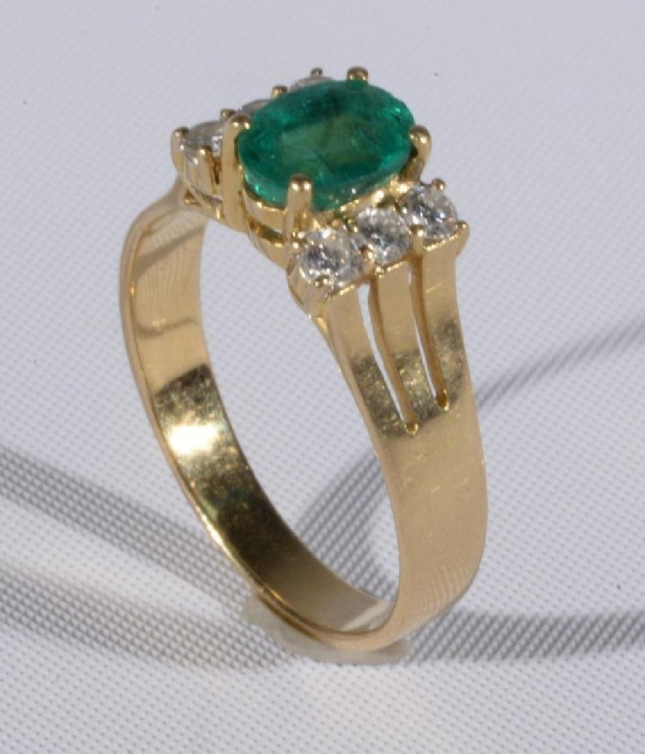 18 karat gold ring set with center oval emerald flanked
