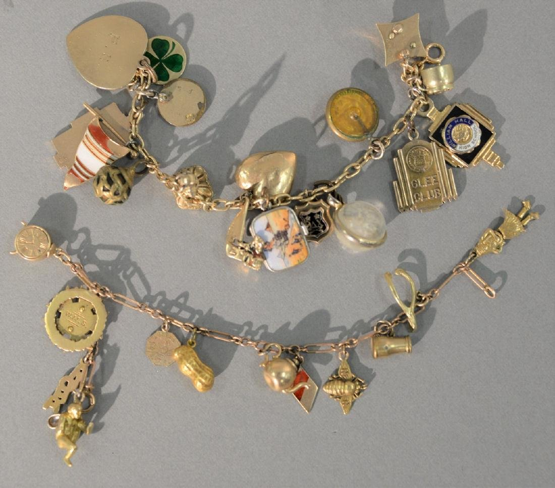Two gold charm bracelets with several gold charms on