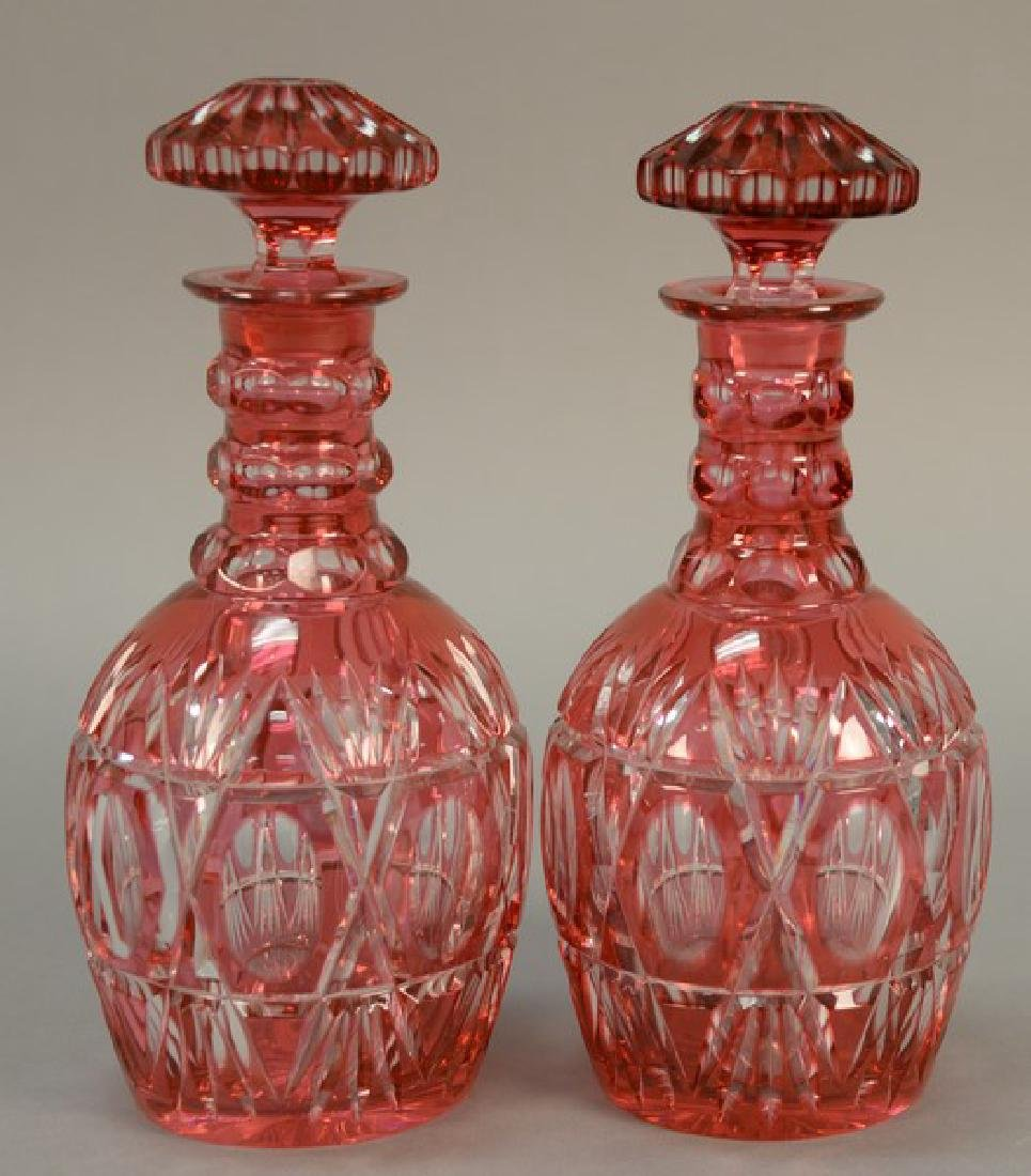 Pair of cranberry cut to clear decanters with stoppers.