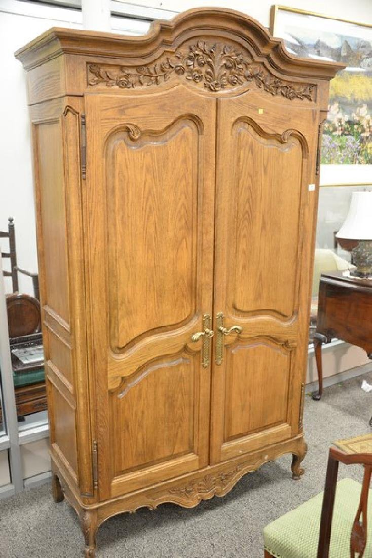 Large oak armoire with two doors and carved top with