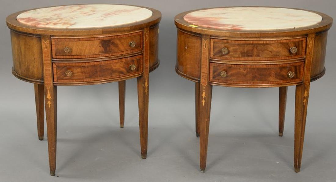 Pair of mahogany oval tables with inset marble tops.