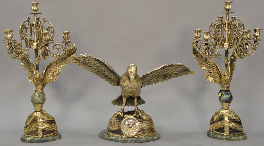Brass three piece clock set having flying bird on