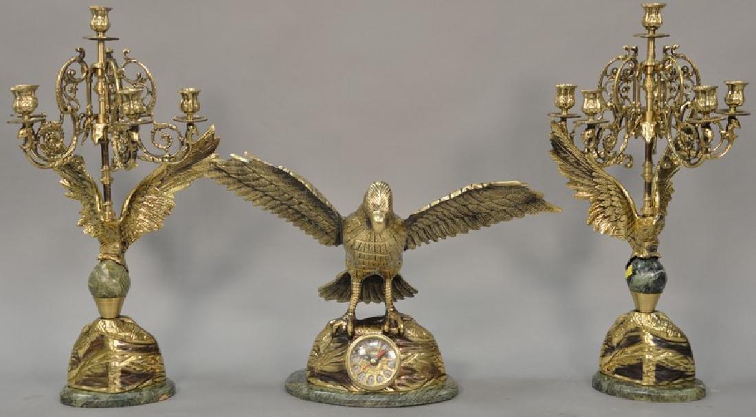 Brass three piece clock set having flying bird on