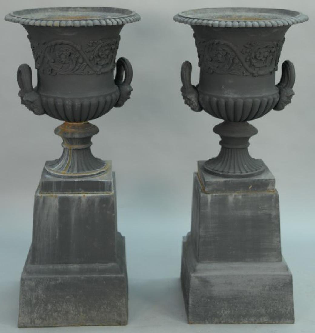 Pair of Victorian iron urns with handles and faces on
