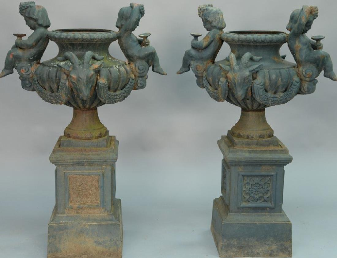 Pair of two part iron urns with putti and ram's heads,