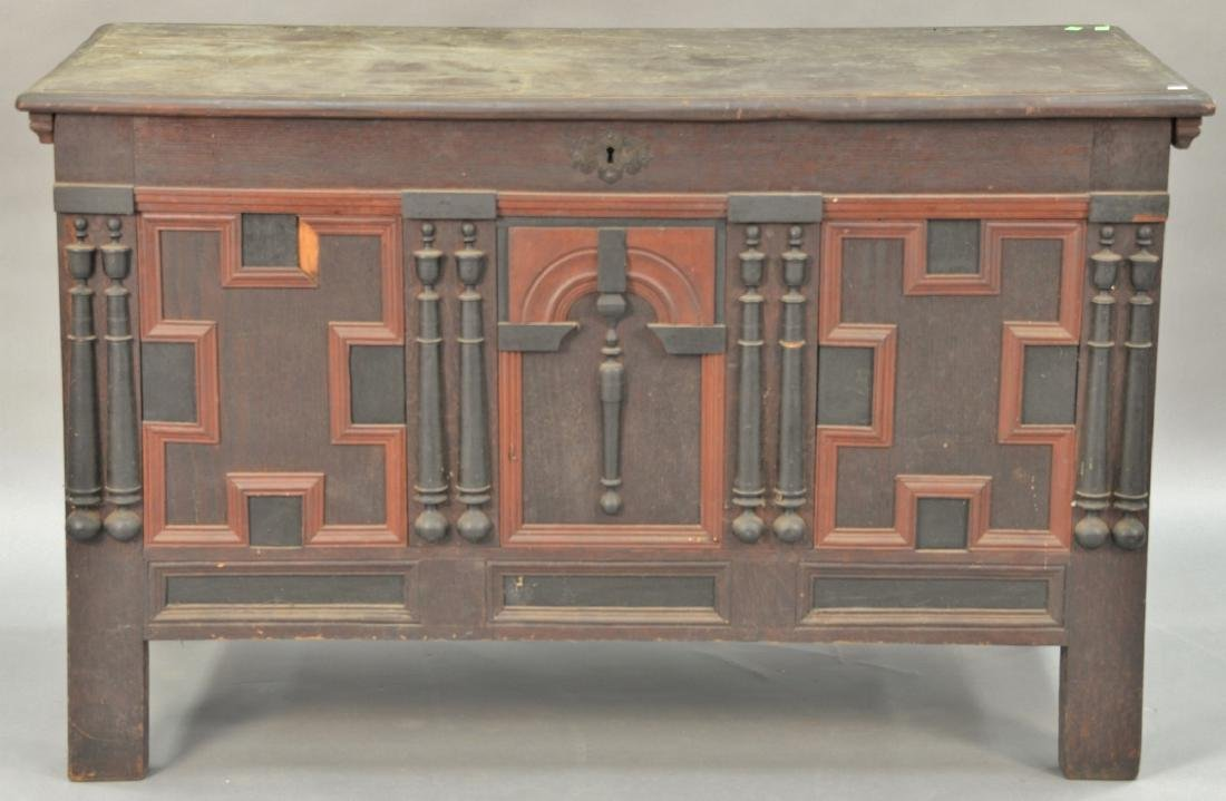 Oak lift top chest with molding and turnings on front.