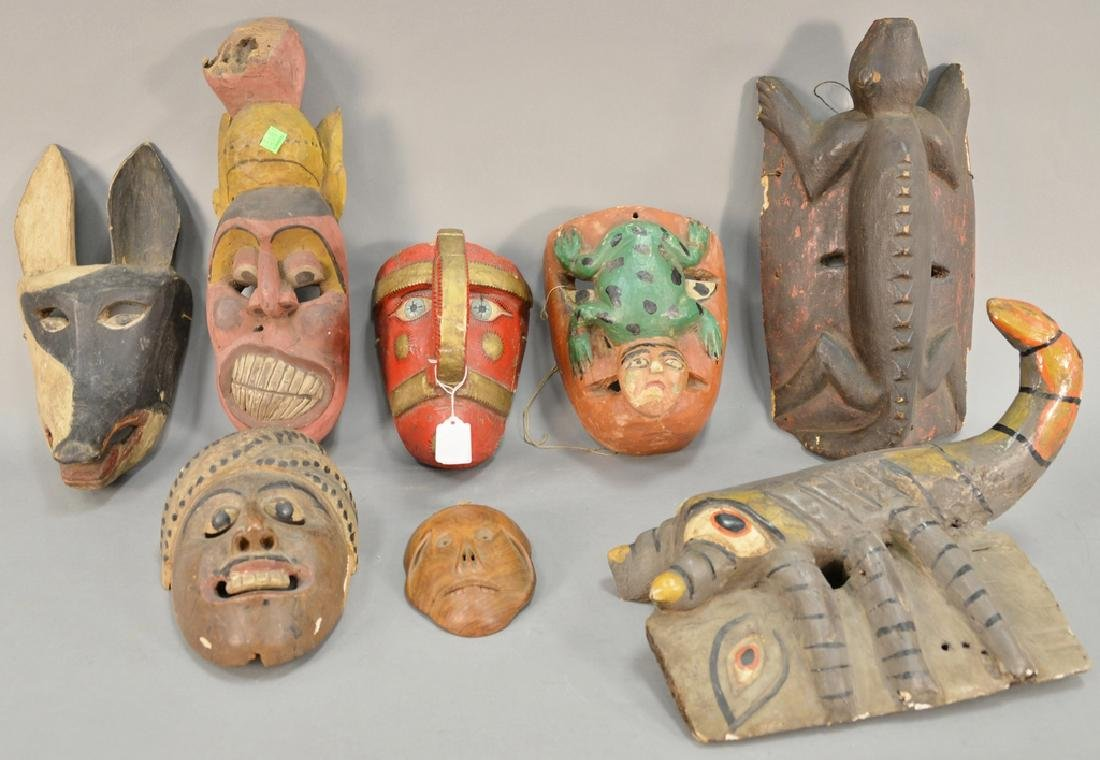 Eight wooden hand carved tribal masks to include a