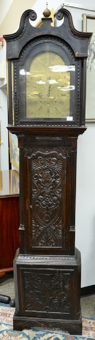 English oak tall clock with carved door and base,