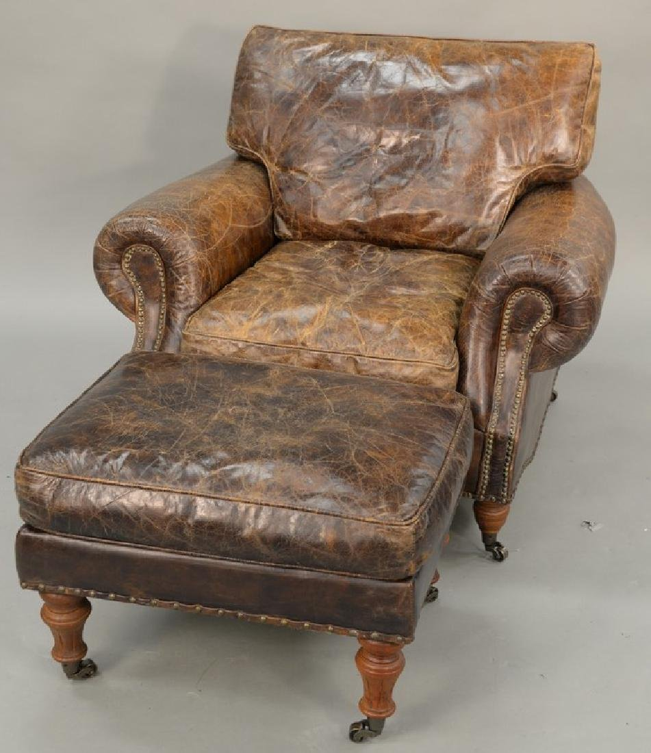 Leather upholstered chair and ottoman. ht. 34 in., wd.
