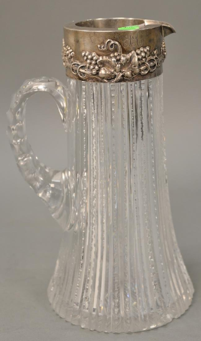 Cut glass pitcher with sterling silver top (chipped).