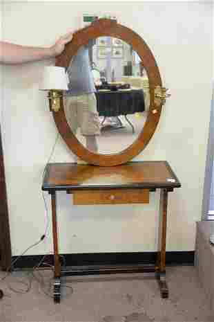 An English yew wood writing table and oval mirror with