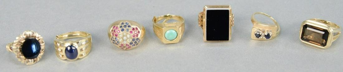 Six gold rings with stones, one with blue stone and