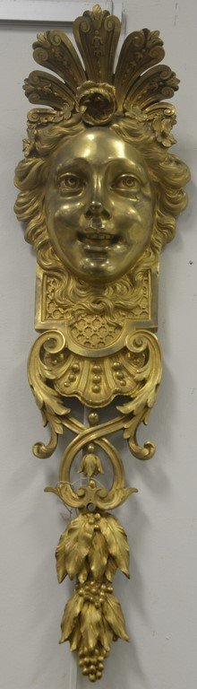 Pair of gilt bronze wall hangings with ladies face over