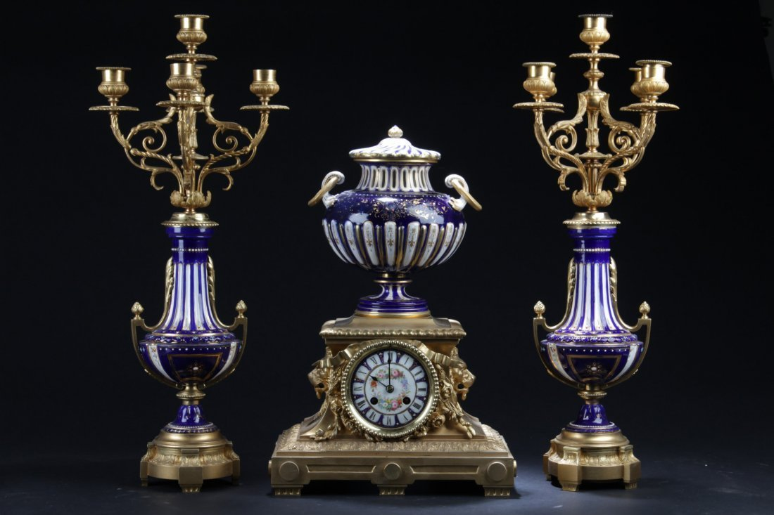 A set of Bronze and Porcelain Table Clock with Two Cand