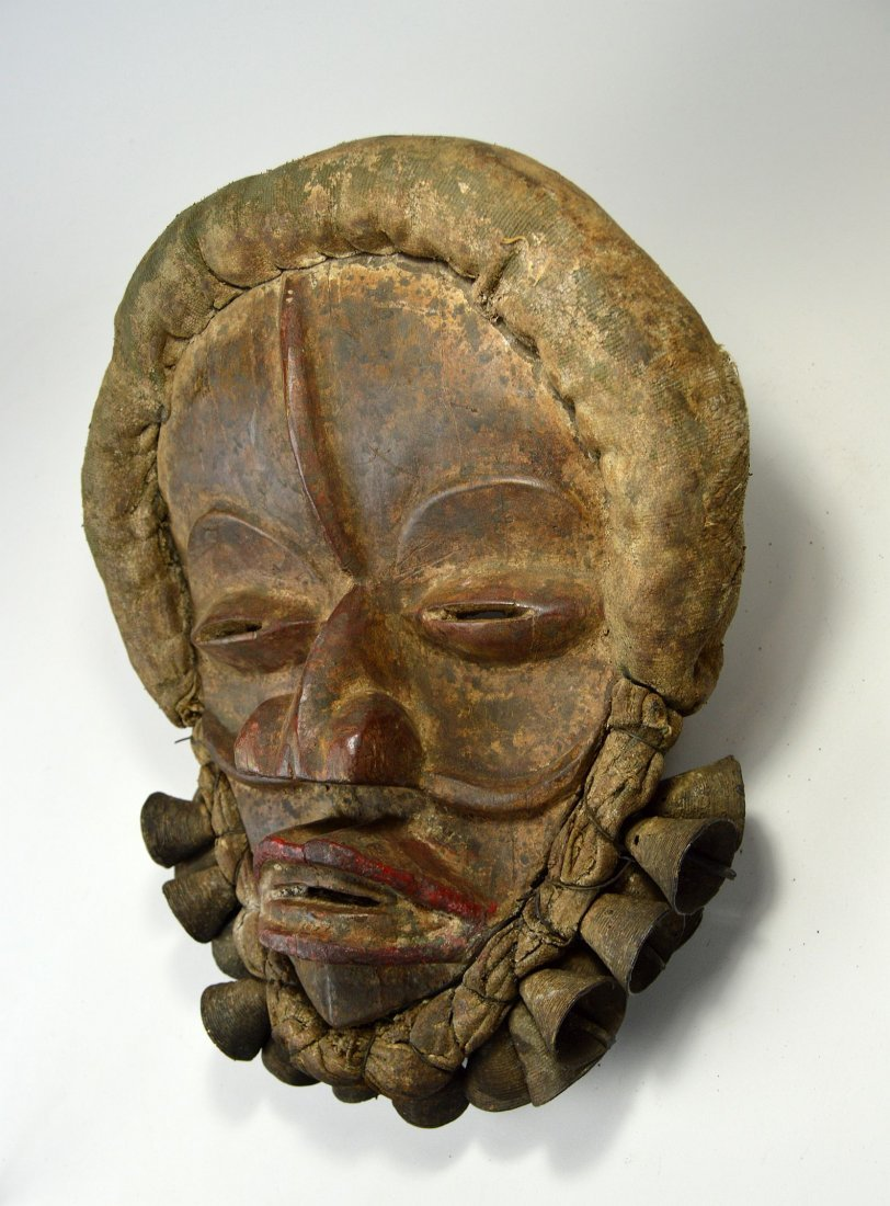 A Dan African mask adorned with Bronze Bells