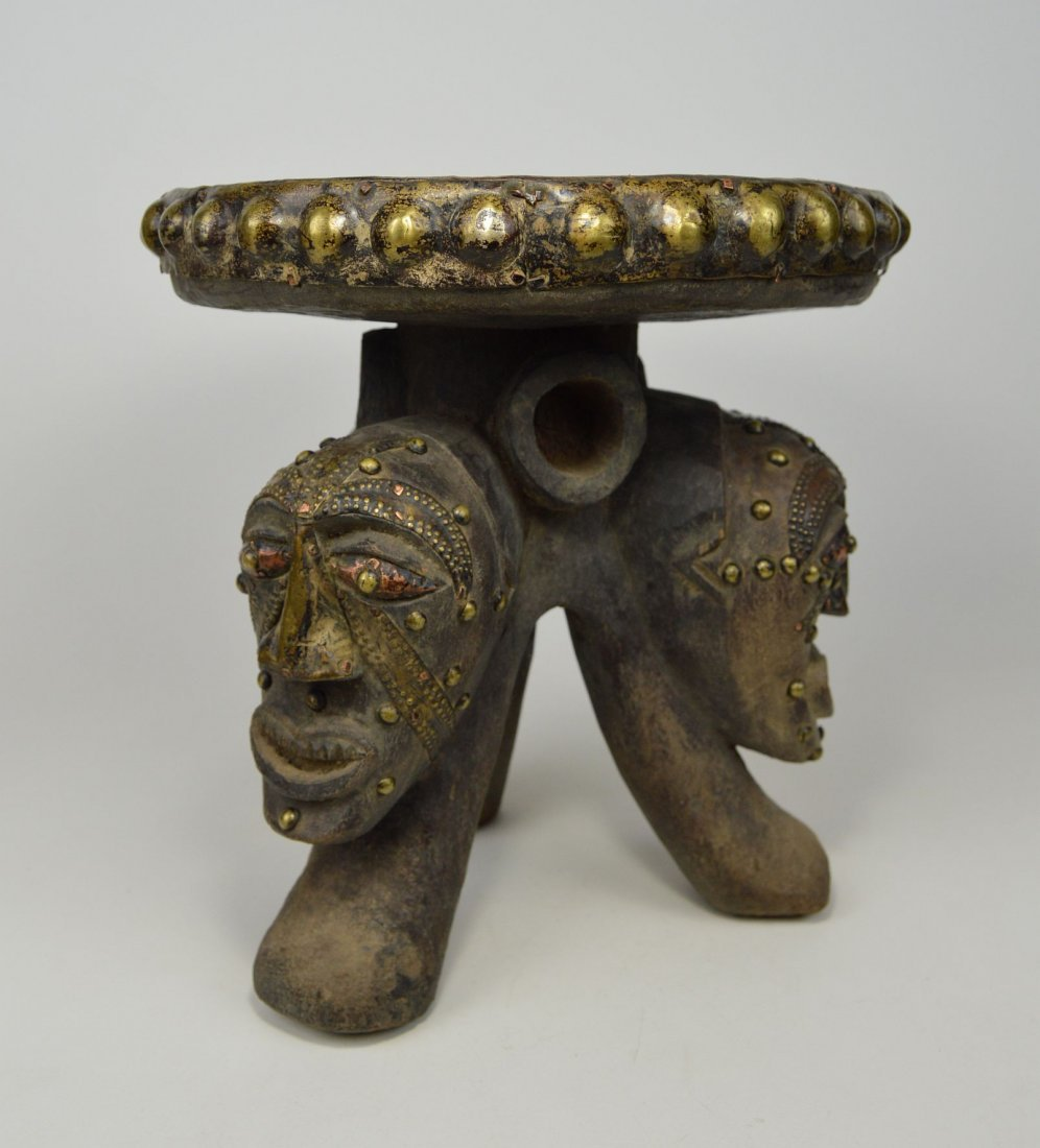 A Songye ceremonial stool with mask faces