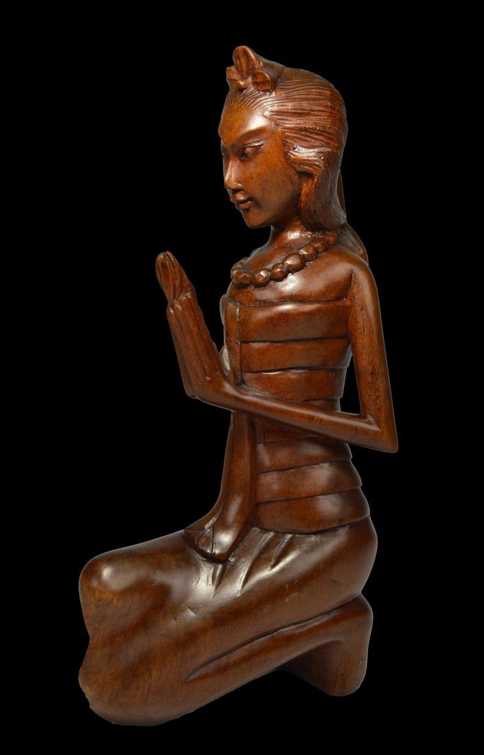 A Serene Carved Wooden Praying Balinese Woman