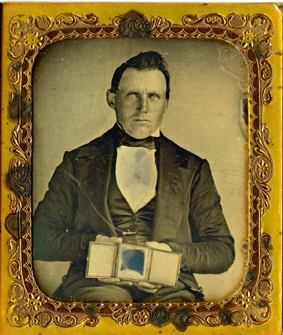 Man holds two daguerreotypes, one in front of other