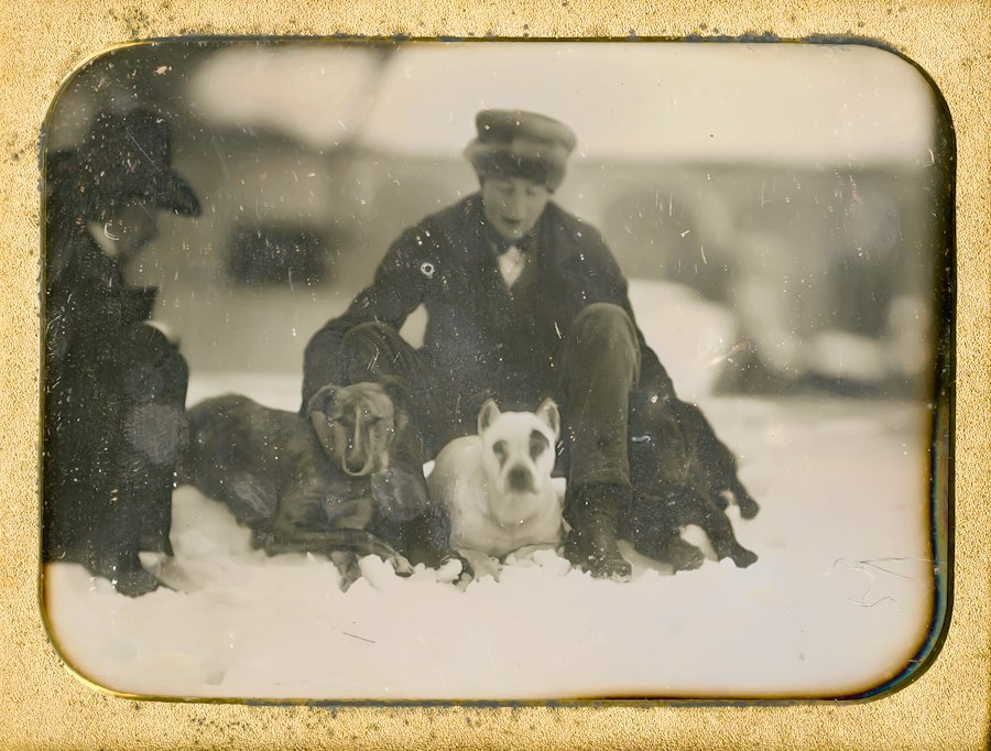 MEN AND DOGS IN THE SNOW.