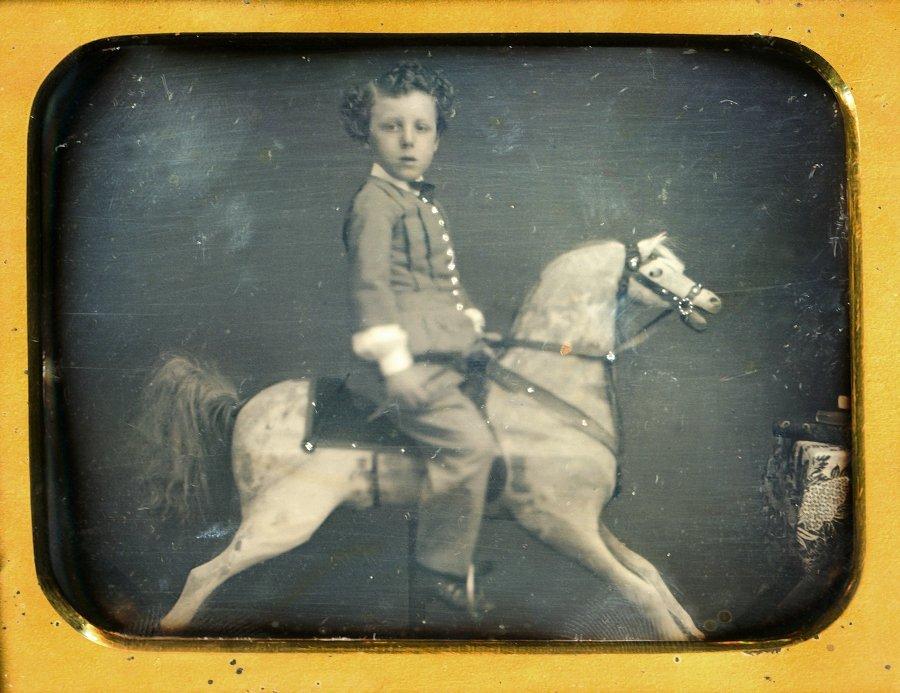 BOY ON HOBBY HORSE.