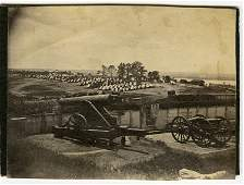 View of an encampment on the banks of a river, with