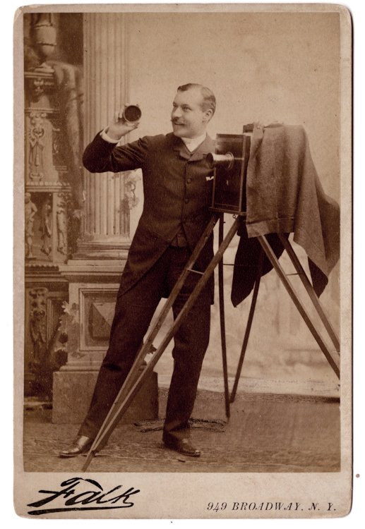 A jaunty photographer with his camera holds the lens