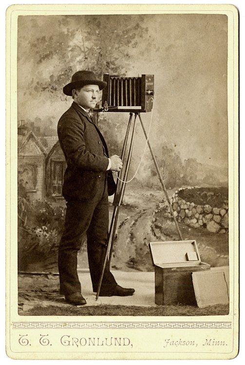 A photographer stands beside his camera.