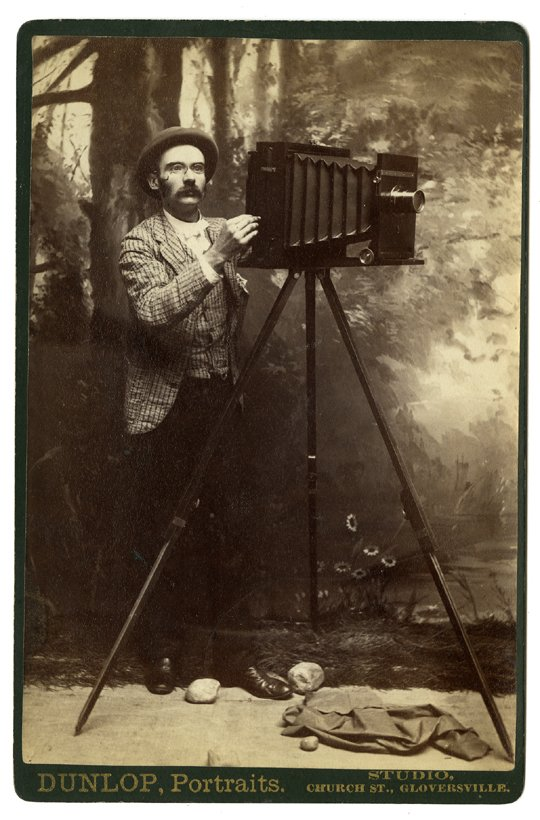 A photographer with a bellows camera, before a