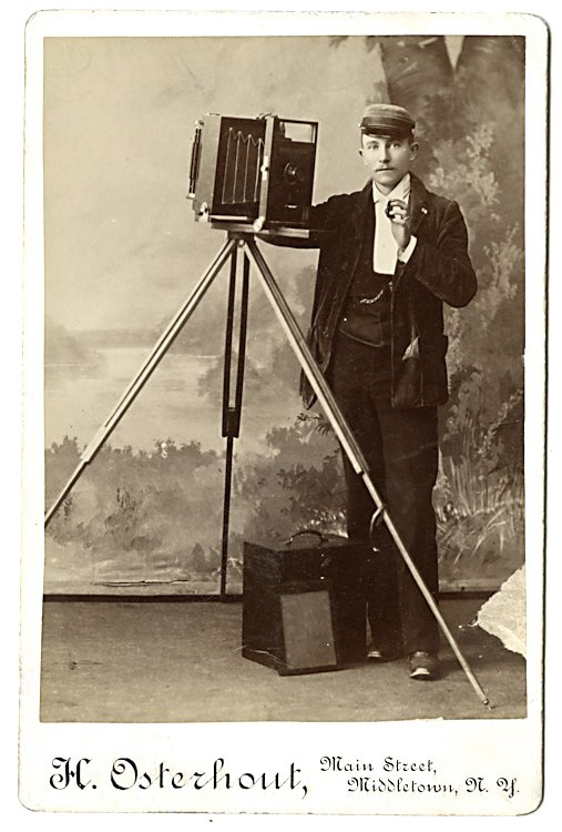 A photographer holds the lens cap delicately.