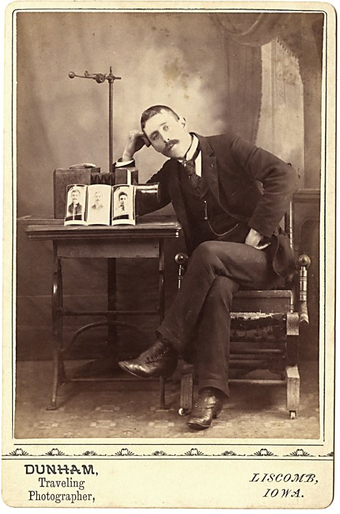A photographer with a camera and cabinet cards on a