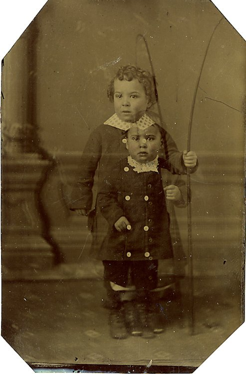 Double exposure. Two babies hold flexible poles.