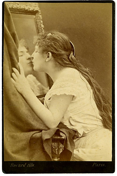 Kissing her reflected image.