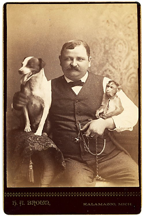 A man holds a dog on one arm, a monkey on the other