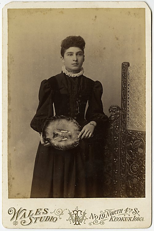 A woman holds a basket with a dead bird in it.