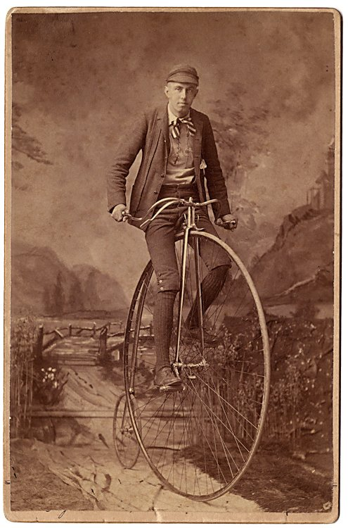 A man is in riding position on his high wheel bicycle.
