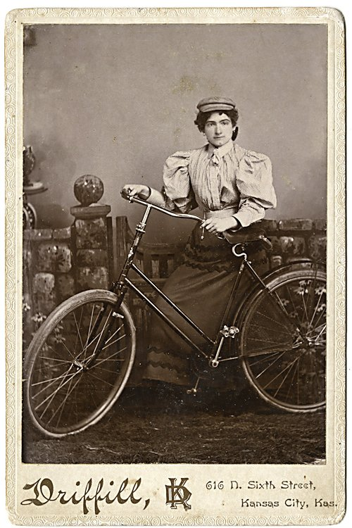 A woman bicyclist with a cap, a full blouse, a long