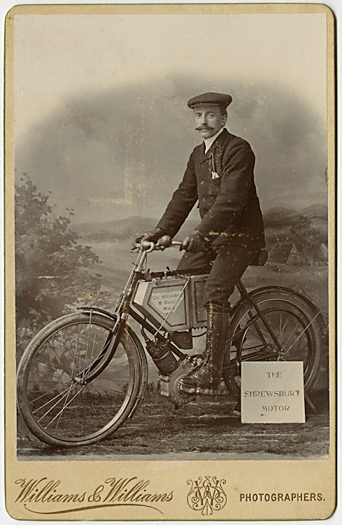 An early motorcycle with its rider.