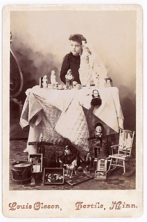 A girl with her doll, toys and other objects on the