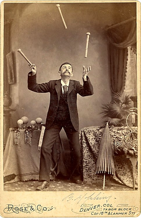 A juggler with sticks up in the air.