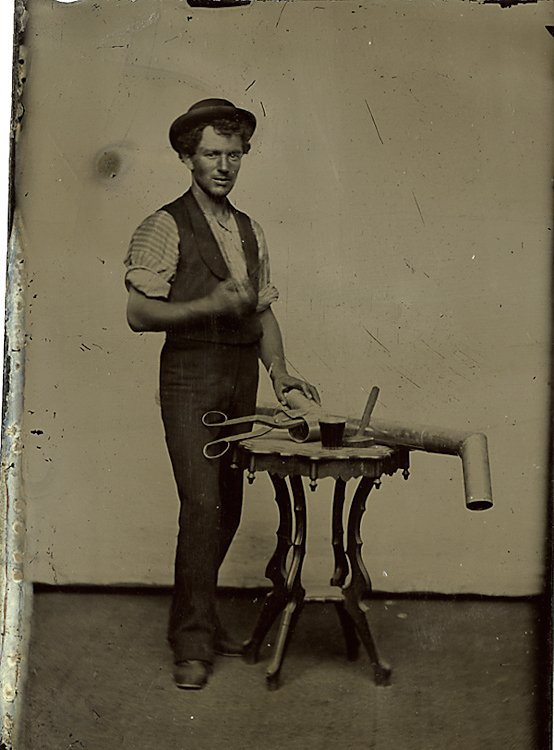 A tinsmith with shears cutting a pipe.