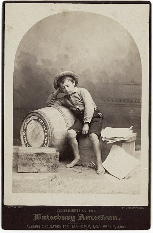 A newspaper boy dozes against a barrel of flour.