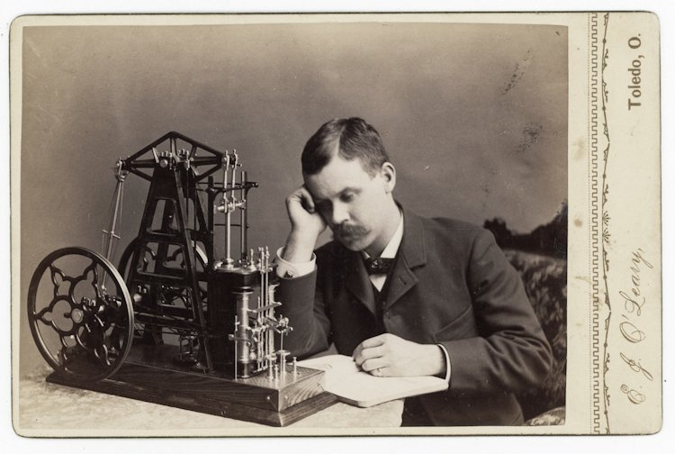 A studious inventor with his model engine.