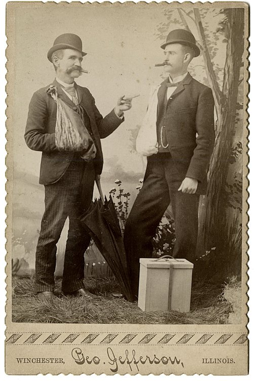 Two men with broken arms, both are smoking cigars.